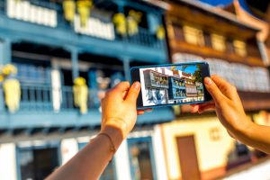 Female hands photographing with smart phone old colorful balconies in Santa Cruz de la Palma in Spain